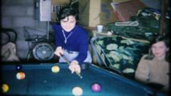 Teenage girls  playing pool in basement rec room, 328 vintage film home movie Stock Footage
