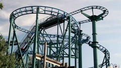 Red roller coaster moving upwards afternoon Stock Footage