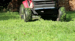 Lady riding as she mows her lawn with her red lawn mower Stock Footage
