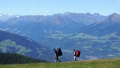 Two paragliders with backpacks walking on the top of the mountains, Italy HD Stock Footage