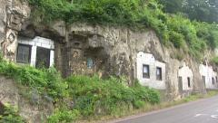 Row of Cave dwellings in Geulhem, the Netherlands + traffic - pan Stock Footage