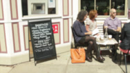 Stock Video Footage of People sitting outside a small cafe on sidewalk (2 of 3)