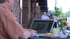 Man typing on his laptop at a sidewalk cafe Stock Footage