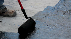 Road men applying asphalt using a roller brush Stock Footage