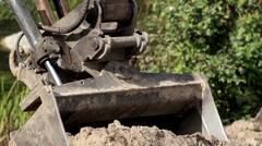 Backhoe carrying some soil and then dropping it off in a pile Stock Footage