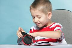 Stock Photo of young cute boy draws with color pencils