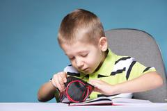 young cute boy draws with color pencils - stock photo