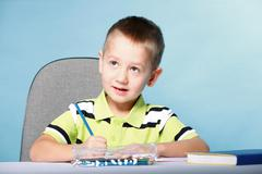 Young cute boy draws with color pencils Stock Photos