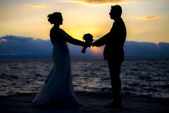 Silhouette of a newly wed couple - stock photo