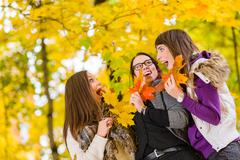 Sisters and maple leaves Stock Photos