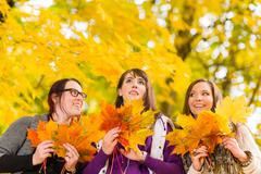 sisters and maple leaves - stock photo