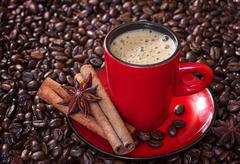 Coffee in a red cup with cinnamon and anise stars. Stock Photos