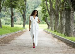 happy young woman walking on the summer park - stock photo