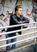Handsome blond haired young man on metal railing Stock Photos