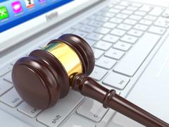 Online judgement. gavel on laptop.  3d Stock Illustration
