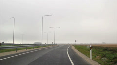 Vehicle moving swiftly on a highway next to an open field Stock Footage