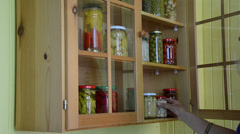 Hand open wooden cupboards door puts jar canned garlic Stock Footage