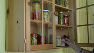 Stock Video Footage of hand open wooden cupboards door puts jar canned garlic