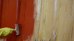 Hand yellow glove paint wooden plank wall with brush red color Stock Footage