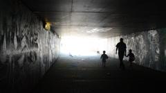 Girls pair man children walk underground dark passage subway Stock Footage