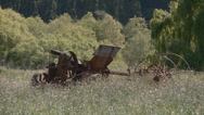 Stock Video Footage of old farm machine rusts in long grass
