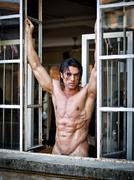 Handsome muscular man naked looking in camera on window frame Stock Photos