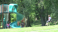 Mom watching children play on slide Stock Footage