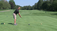 Golfer driving ball down fairway - stock footage