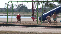 Kids playing on playground at beach Stock Footage