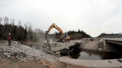 540 bulldozer destroying a bridge backhoe working on the damaged bridged Stock Footage