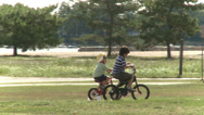 Stock Video Footage of Kids Riding Bicyles in the Park (2 of 6)