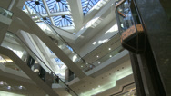 Stock Video Footage of Watching elevator descend from glass ceiling within mall (1 of 2)