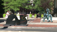 Stock Video Footage of Woman walking by sculptures on pathway