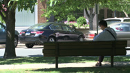 Stock Video Footage of Man sitting on park bench downtown (2 of 2)