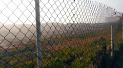 Los Angeles Sand Dune and Fog Through Urban Chain link Fence - stock footage