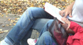 Woman reading a Book vs Child Playing on Tablet, Modern Device on Bench in Park Footage