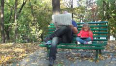 Man Reading Newspaper, Child Playing on Tablet, Ipad, Gadget on Bench in Park Stock Footage