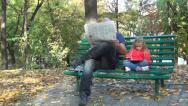 Stock Video Footage of Man Reading Newspaper, Child Playing on Tablet, Ipad, Gadget on Bench in Park