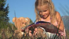 Little Girl Laughing Reading a Storybook, Child Playing with Book, Meadow Grass - stock footage
