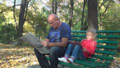 Man Reading Newspaper on Bench in Park, Child Reading Storybook with her Father - stock footage