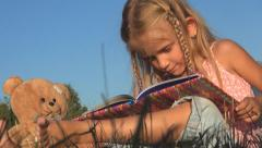 Little Girl Reading a Storybook, Child, Bear Playing with Book on Meadow Grass - stock footage