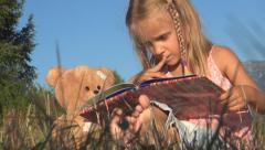 Little Girl Reading a Storybook, Child, Bear Playing with Book on Meadow Grass Stock Footage