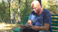 Man with Tablet, Person Sliding on Computer Device on Bench in Park, People HD Footage