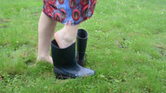 Barefoot woman on meadow grass boot welly rubber shoes and walk Stock Footage