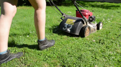 Woman cut grass lawn with mower cutter Stock Footage