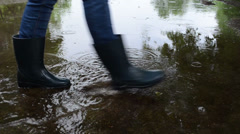 Air bubbles on poll soak water and woman in gumboots cross it - stock footage