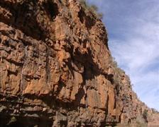 Steep wall, red rock escarpment of Katherine Gorge - tilt down River Stock Footage