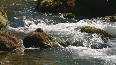Water cascades  over rocks in a stream Stock Footage