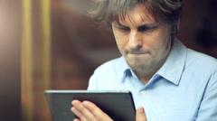 Mies käyttää tabletti tietokoneen kosketusnäyttö kahvilassa Arkistovideo