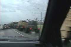 U.S. Army relief convoy POV through windshield wipers, rain. Hurricane Andrew Stock Footage